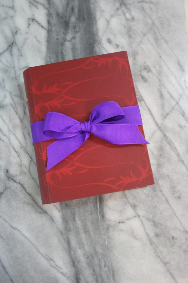 picture of a gift box of chocolates that looks like a book with a purple ribbon sitting on a marble slab