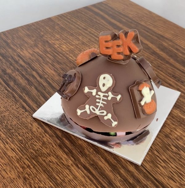 Photograph of a chocolate Halloween Smash cake with lollies inside and chocolate skeletons decorating the exterior