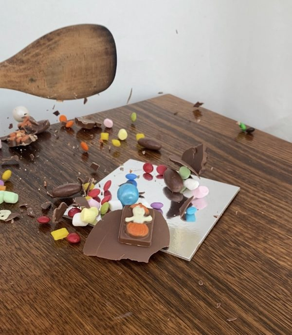 Smashing a Halloween chocolate smash cake with a wooden spoon