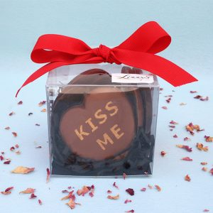 A clear box with six written messaged hearts inside and a red bow on top