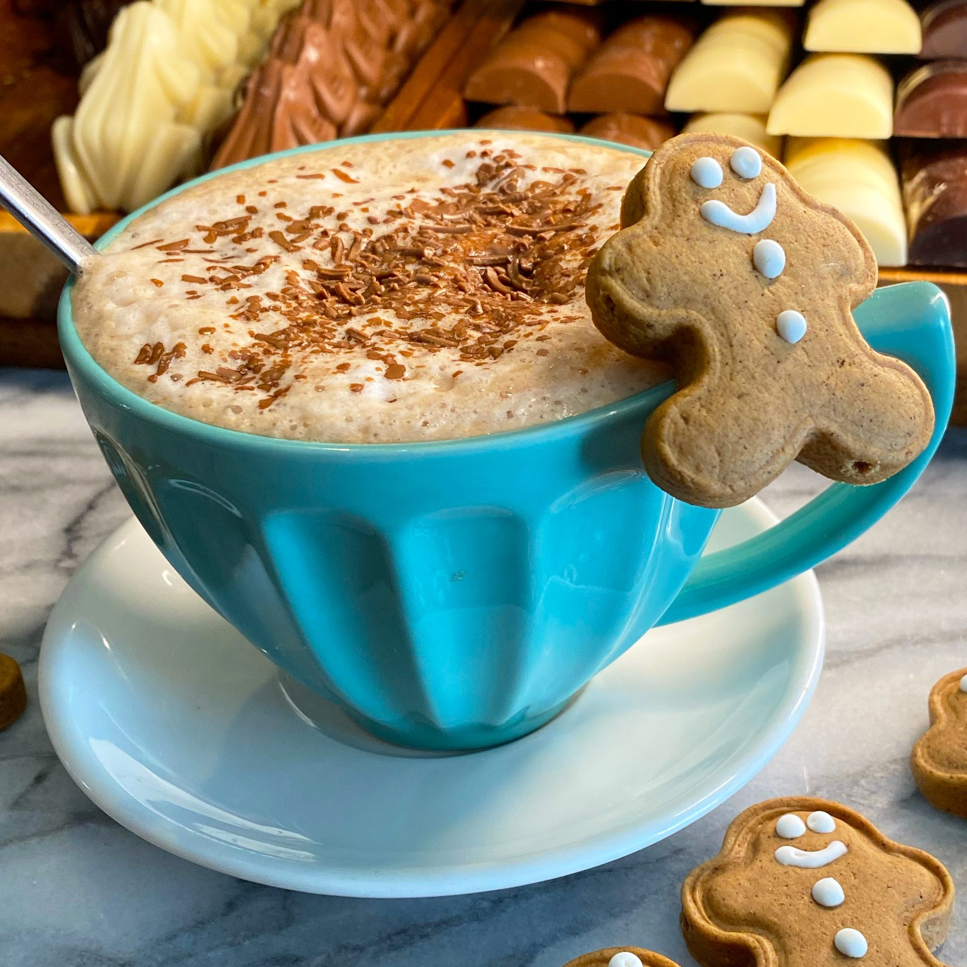 gingerbread hot chocolate in mug with mini gingerbread biscuits surrounding