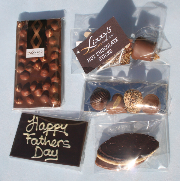 contents of the hamper box sprawled out from left to right hazelnut slab, hazelnut hot chocolate stick, fathers day plaque, mixed chocolates, and nougatines
