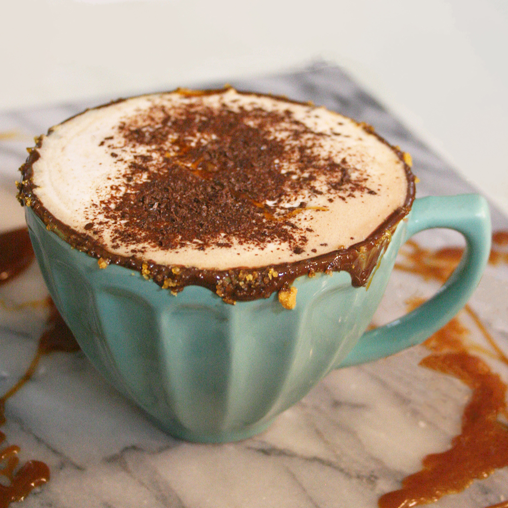 salted caramel hot chocolate in mug with salted caramel surrounding the base